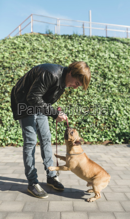 young man playing with french bulldog