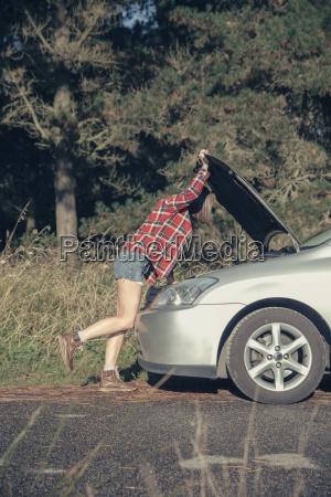 young woman examining damaged car