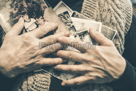 hands of senior woman holding old