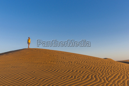 woman walking over sand dunes