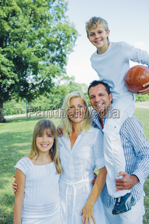 portraet einer gluecklichen familie im park