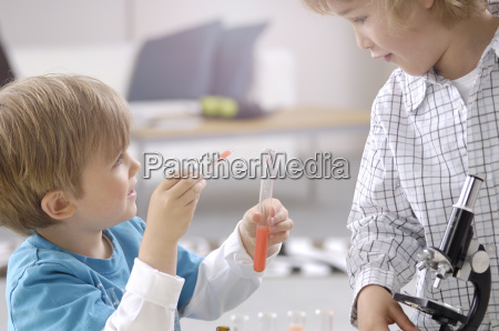 two little boys playing with utensils
