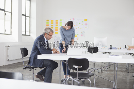 businessman and two in office looking