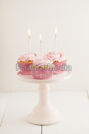 three pink cup cakes with lighted