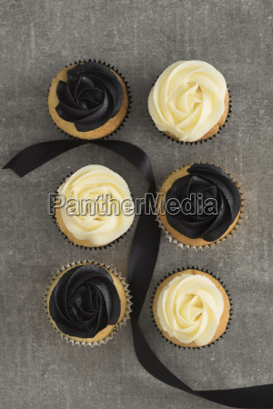 six cup cakes with black and