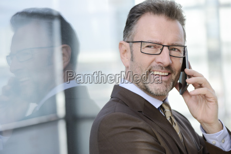 portrait of smiling businessman telephoning with