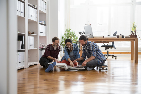three creative business people sitting on