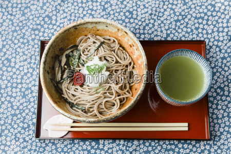 bowl of soba noodles on red