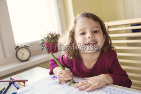 portrait of smiling little girl painting