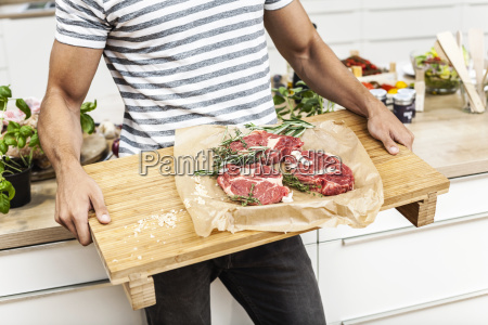 man carrying wooden tray with steaks