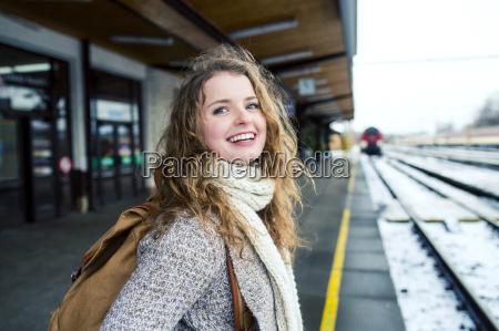 laechelnde teenager maedchen auf station plattform