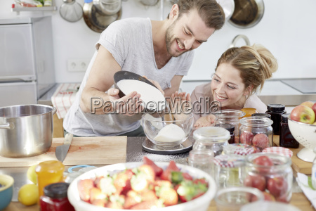 couple in kitchen pouring sugar into