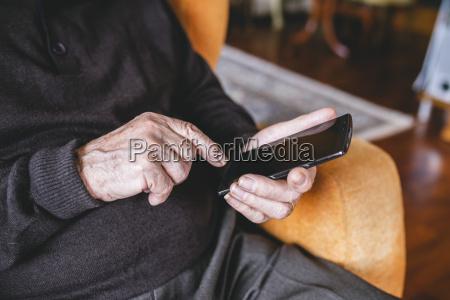 hands of aelterer mann mit smartphone