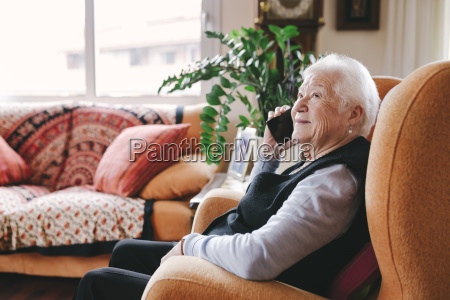 smiling senior woman telephoning with smartphone