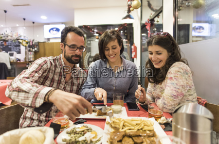 three friends eating spanish food in