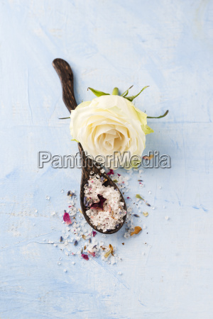 white rose blossom and wooden spoon