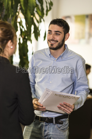 smiling man with woman in office