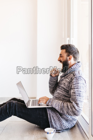 bearded young man working at home
