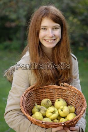 portrait of smiling girl holding wickerbasket