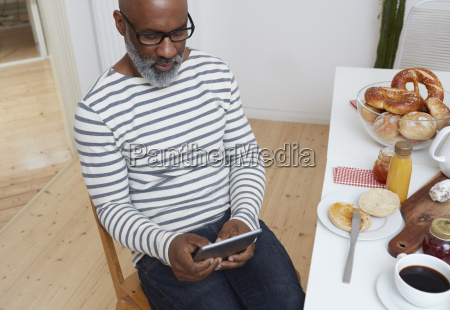 man sitting at laid breakfast table