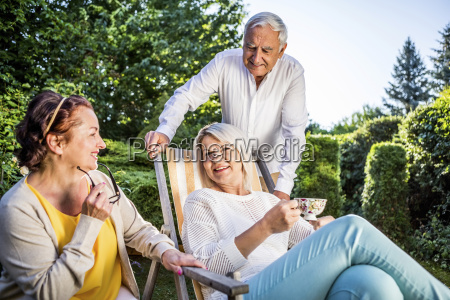 elderly friends relaxing in garden