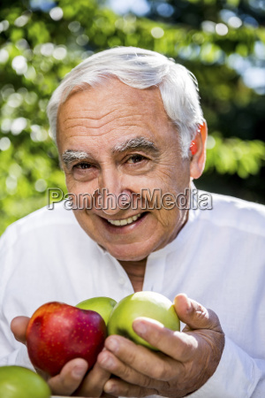 smiling senior man holding apples outdoors