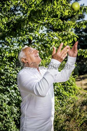 smiling senior man throwing an apple
