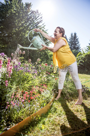 smiling mature woman watering flowers in