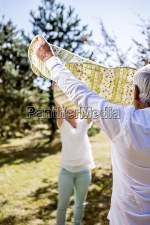 elderly couple holding picnic blanket on
