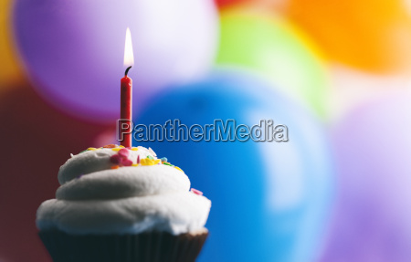 birthday cup cake with lighted candle