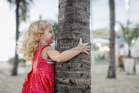 happy girl hiding behind palm tree