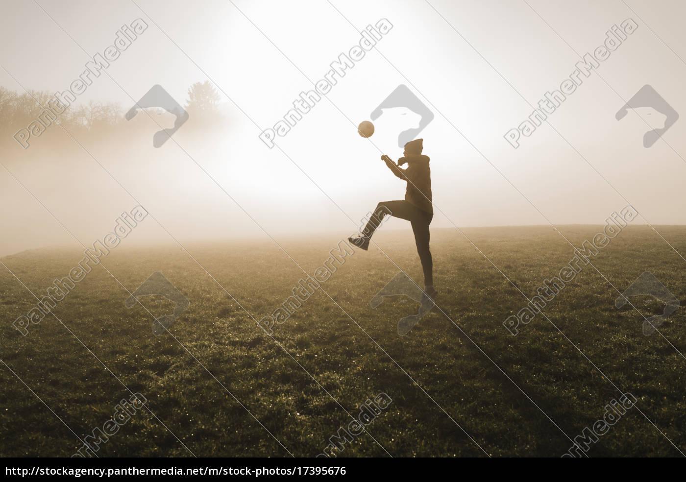 junger mann,der fußball auf wiese am abend spielt - Lizenzfreies ...