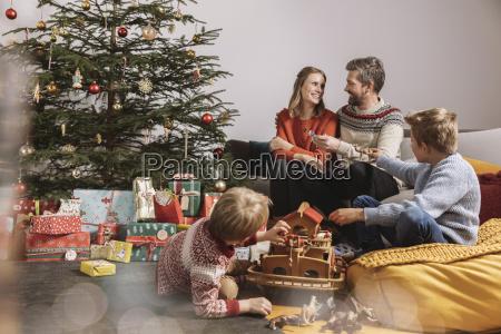 familie von vier auspackt weihnachtsgeschenke und