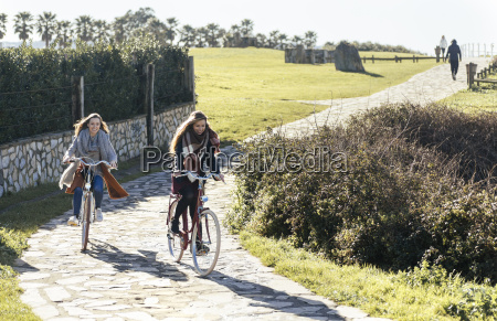 two young women riding bicycle along