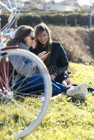 two young women outdoors listening to