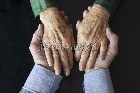 senior couple holding hands close up