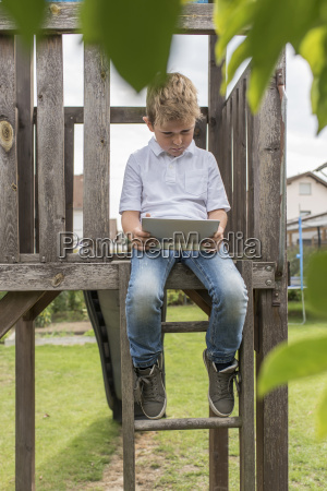 little boy sitting on playgroung equipement