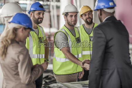 construction worker and executive shaking hands