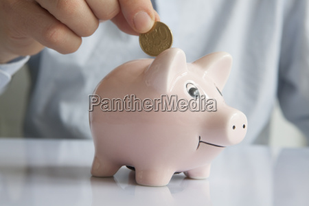man putting coin into piggy bank