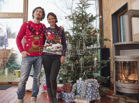 paar steht vor weihnachtsbaum tragen weihnachtspullover
