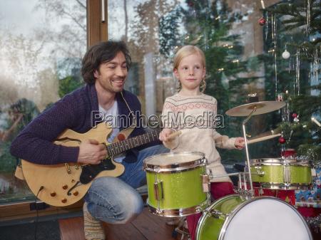 vater und tochter musizieren an heiligabend