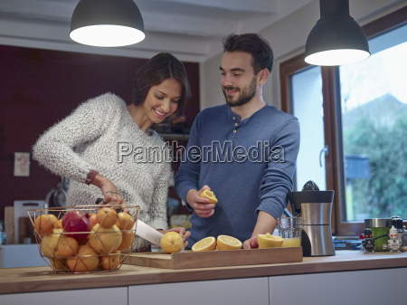 couple in kitchen slicing oranges for
