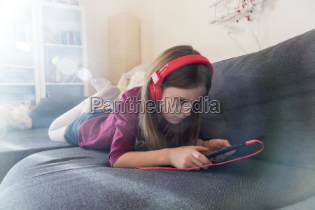 girl lying on the couch listening