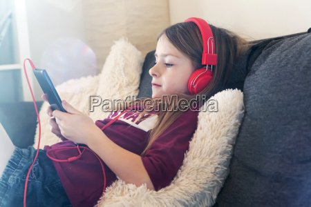 girl sitting on the couch listening