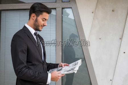 businessman wearing black suit reading newspaper