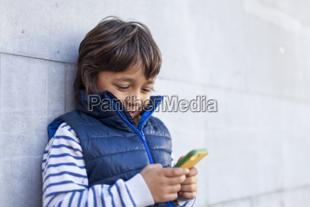 portrait of boy leaning against wall