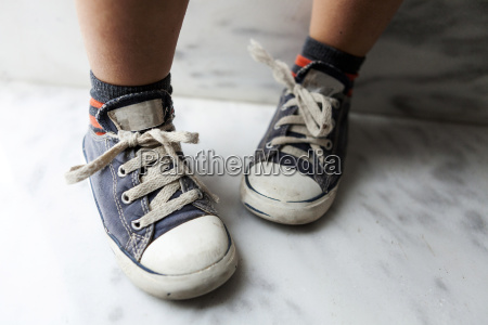 close up of boy wearing sneakers