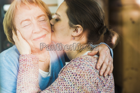 young woman kissing senior woman behind