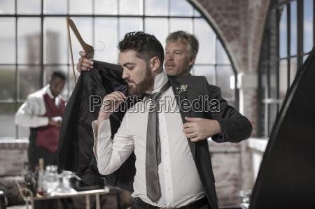best man helping groom getting ready