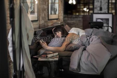 frau schlaflos im bett schaut auf